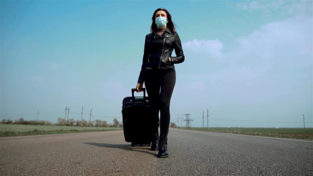 alone woman in face protective mask walking on median strip in middle of road with suitcase on wheels - donna valigia solitudine video stock e b–roll