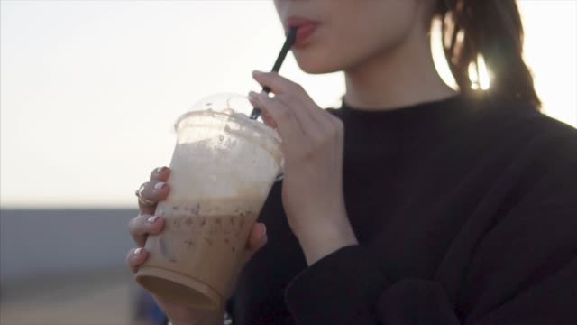 alone woman is drinking coffee, holding cup in hands outdoors in summer evening - paglia video stock e b–roll