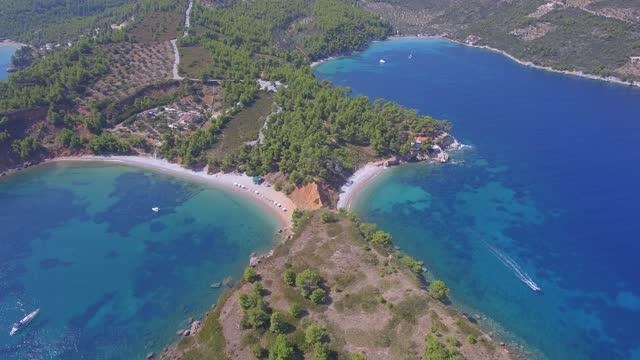Alonissos, Greece double side beach Aerial shot of the double side beach of kokinopetra in Alonissos, Greece aegean sea stock videos & royalty-free footage