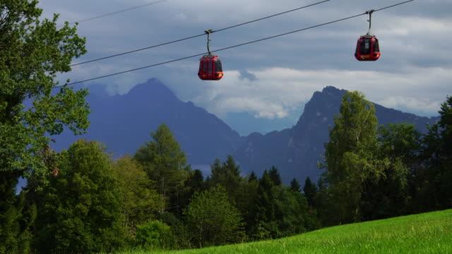 Alpine cable car gondola passing Lake Lucerne hills of Pilatus in Swiss Alps in Switzerland video