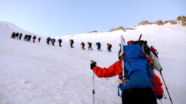alpine climber is watching the team climbing  in the peak of mountain in winter - esploratore video stock e b–roll