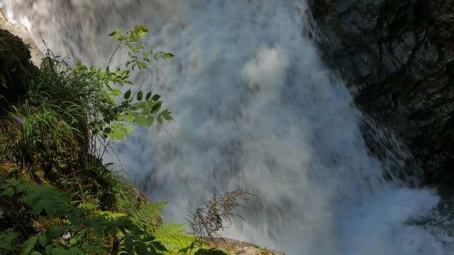 stockvideo's en b-roll-footage met alpine rivier waterval in de franse en zwitserse alpen met vegetatie verplaatst door de wind en een doofheid lawaai - zermatt