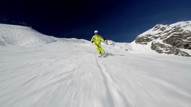alpine skier skiing in short swings behind camera video