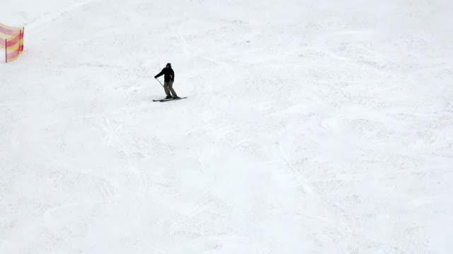 alpine skier skiing swings on ski slope on winter day video