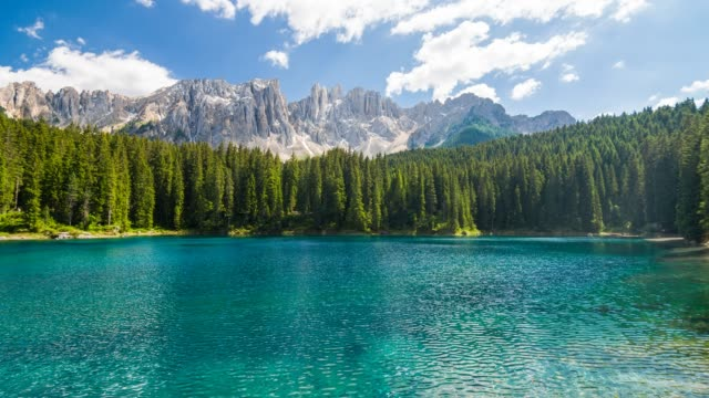 Alpine turquoise Carezza lake with Latemar mountain range in background, Trentino in Dolomites, Italy