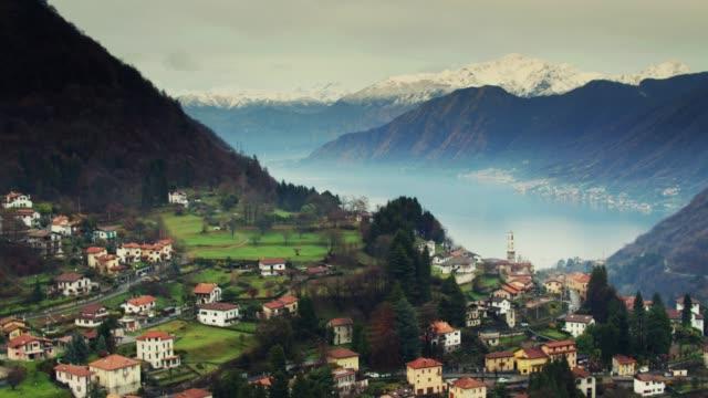 alpine village with lake como reveal - drone shot - lombardia video stock e b–roll