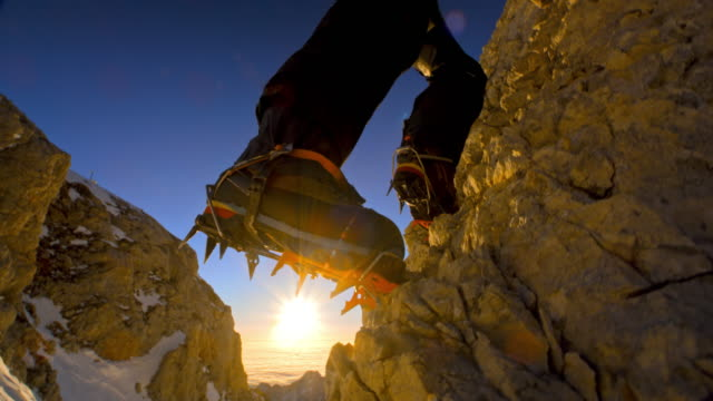 Alpinist climbing the mountain peak in sunshine Medium handheld low angle shot of an alpinist climbing the rocky mountain peak with sun shining behind him. conquering adversity stock videos & royalty-free footage