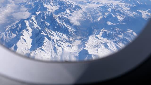 Bидео Alps mountains peak view through aircraft window