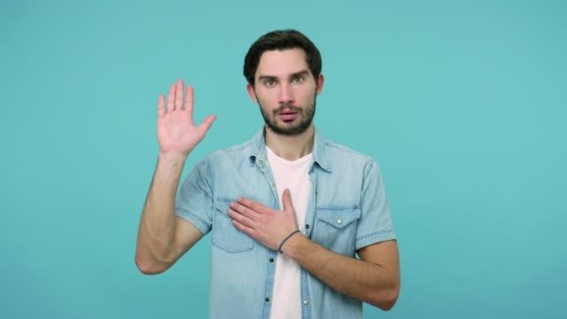 stockvideo's en b-roll-footage met oké, ik zweer het! geërgerde bebaarde kerel in jeansoverhemd dat hand opheft om belofte te geven, ongewild het nemen van eed - swearing