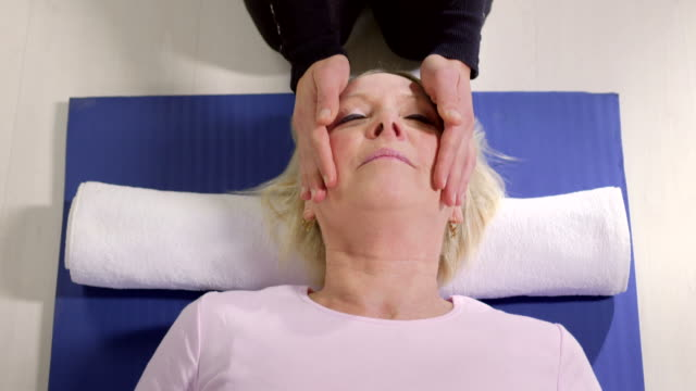 Alternative medicine, young therapist doing reiki therapy to senior woman video