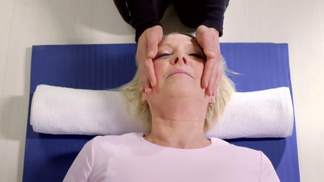 Medicina alternativa, terapia de joven haciendo reiki la terapia para la mujer mayor - vídeo