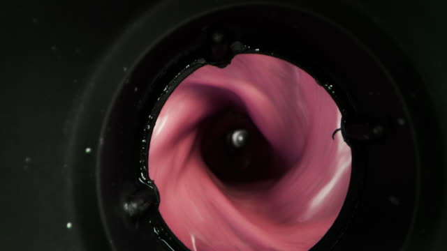Alternative view of mixing dietetic milkshake with fresh biologic blueberries and raspberries in slow motion.