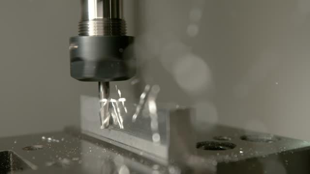makro: aluminiumspån kommer flygande av ett litet arbetsstycke under pinnfräsning. - cnc maskin bildbanksvideor och videomaterial från bakom kulisserna