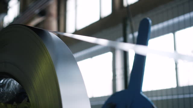 Aluminum metal tape is packed in bobbin and mounted on rotating machine, edge of tape is pulled into machine mechanism, gradually bobbin is unwound, metal goes to processing