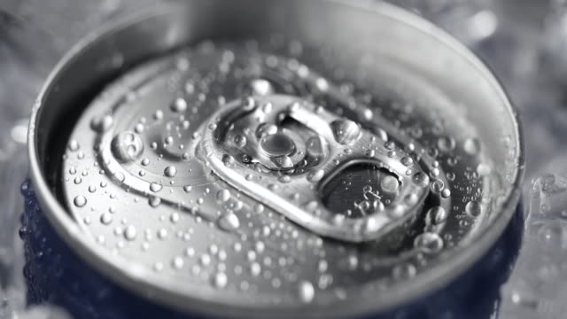 Aluminum soda can lid cover of soft drink and ice close-up rotation