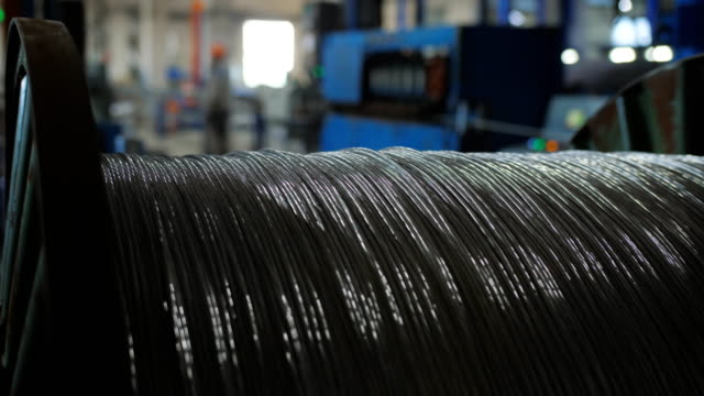 aluminum wire pulley rolling. winding the aluminum cable onto the reel. - alluminio video stock e b–roll
