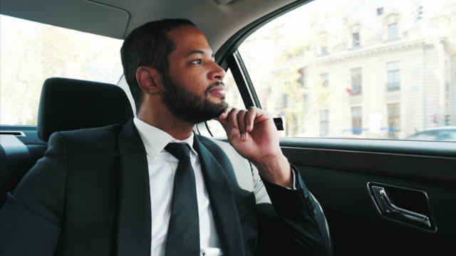I always admire the city when Im traveling. Young businessman traveling by car. He is enjoying the city life with every journey. ceo stock videos & royalty-free footage