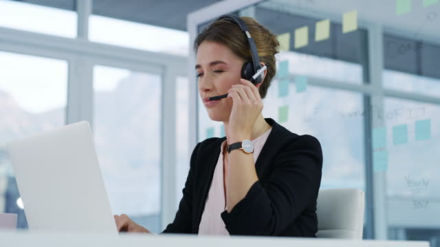 Always at your service 4k video footage of an attractive young businesswoman sitting in her office and wearing a headset while using a laptop hands free device stock videos & royalty-free footage
