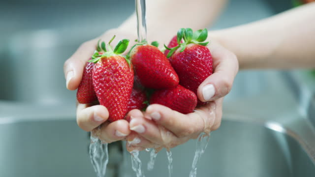 Always clean your fruit and veggies before consumption 4k video footage of an unrecognizable woman washing a bunch of strawberries in her kitchen sink at home kitchen sink stock videos & royalty-free footage