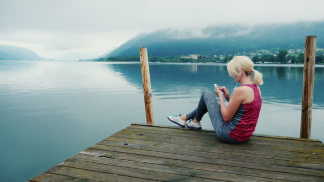 Always connected. A woman uses a smartphone, sits in a picturesque place near a mountain lake in the Alps video