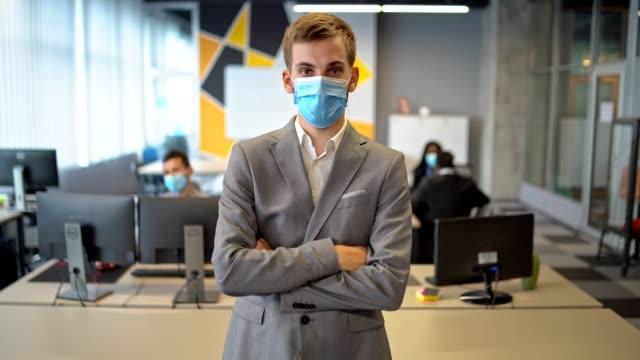 vincerò - uomo d'affari sicuro di sé che indossa maschere protettive nel suo ufficio e guarda la telecamera - braccio umano video stock e b–roll