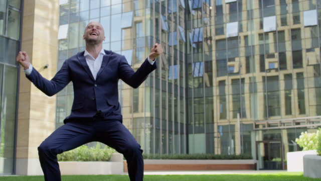 I am the winner Shot of a cheerful young businessman jumping and smiling in front of camera while cheering the success outside of an office complex. Recorded at 90 fps good news stock videos & royalty-free footage