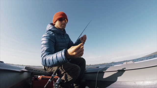 Amateur angler catches zander Amateur angler fishing on the lake from the boat fishing rod stock videos & royalty-free footage
