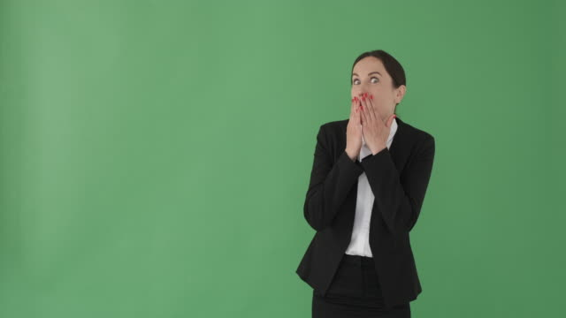 Amazed businesswoman advertising product on green screen