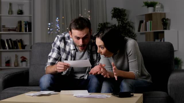 amazed couple reading good news on a receipt - bills and taxes stock videos & royalty-free footage