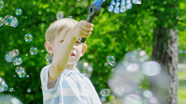 Amazed Little Kid Blowing Lots of Bubbles Outdoor video