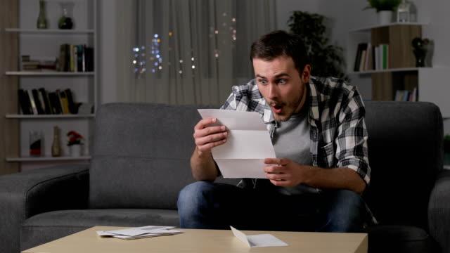 vidéos et rushes de homme étonné lire de bonnes nouvelles sur lettre - bec