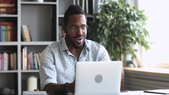Amazed young african man read great news online on laptop