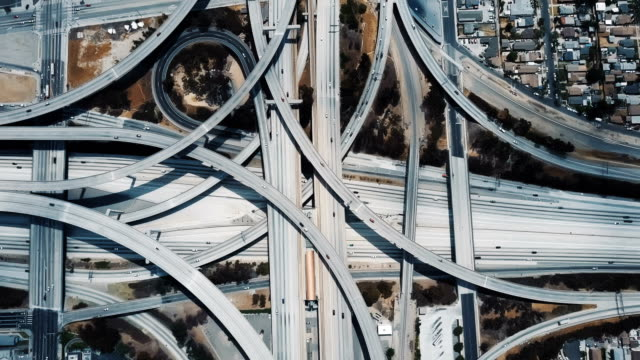 amazing aerial lockdown view of cars moving through large complex highway junction interchange in los angeles, usa. - black and white architecture stock videos & royalty-free footage