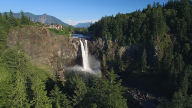 amazing aerial of rainbow in snoqualmie falls with mount si background - parco nazionale video stock e b–roll