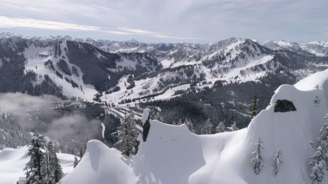 Amazing Aerial Reveal of Highway to Winter Ski Resort with Snowy Mountain Range Peaks video