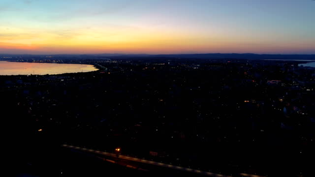 vídeos de stock e filmes b-roll de amazing aerial view drone flying over city after sunset at night - drone shipyard night