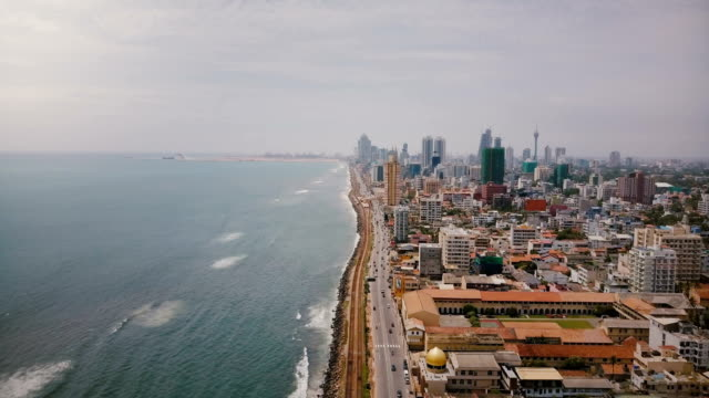 Amazing aerial view of Colombo, Sri Lanka. Drone flying over busy city street, ocean waves and modern Asian architecture Amazing aerial view of Colombo, Sri Lanka. Drone flying over busy city street traffic, ocean coastline and waves, modern Asian urban architecture. Beautiful cloudy sky panoramic view. colombo stock videos & royalty-free footage
