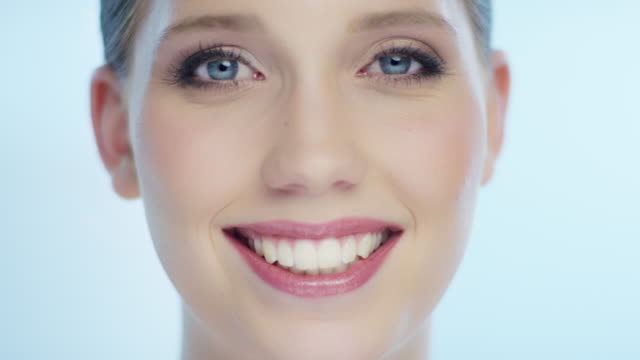 amazing attractive young woman smiles into the camera and shows her teeth - denti video stock e b–roll