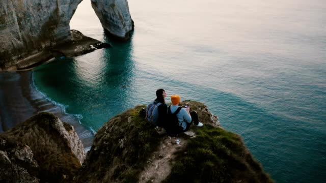 Amazing cinematic aerial shot of happy romantic couple watching sunset sea sitting on top of famous Normandy shore cliff Amazing cinematic aerial shot of happy romantic couple watching sunset sea sitting on top of famous Normandy shore cliff. Man and woman enjoying moments of freedom and friendship enjoying travel. normandy stock videos & royalty-free footage