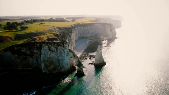 Amazing drone panorama of epic natural rocky arches and pillars at famous white chalk seaside cliffs of sunset Etretat. Amazing drone panorama of epic natural rocky arches and pillars at famous white chalk seaside cliffs of sunset Etretat. Cinematic aerial shot of backlit alabaster rocks and azure bay in Normandy. normandy stock videos & royalty-free footage