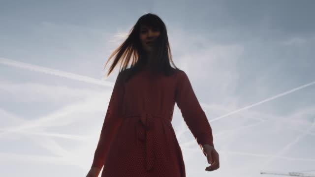 vídeos y material grabado en eventos de stock de increíble toma de ángulo bajo de hermosa mujer sonriente con vestido rojo posando al amanecer torre eiffel vista del cielo a cámara lenta. - moda parisina