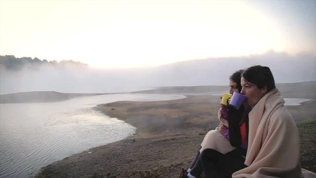 vídeos y material grabado en eventos de stock de increible mañana en lago brumoso! dos amigos bebiendo té y hablando sobre el lago en la mañana - café bebida