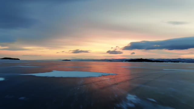vídeos de stock e filmes b-roll de amazing northern frozen lake drone flying with reflection red sunrise on ice 4k. - lago baikal