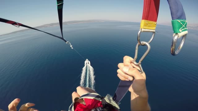 Amazing parasailing over Adriatic sea Croatia. First person view of parachute slings and bar with carabiners high above crystal blue water