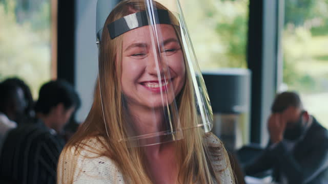 Amazing portrait of young happy Caucasian business woman wearing plastic face shield laughing at workplace slow motion.