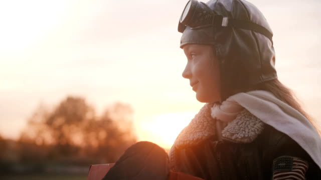 Amazing portrait shot of little girl in fun plane pilot toy costume smiling, looking away with shy calm eyes slow motion