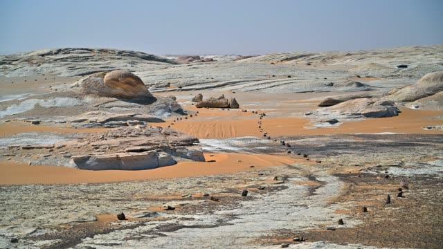 şaşırtıcı rock ve kumul beyaz çöl sahara, egypt - bir orta yetişkin erkek sadece stok videoları ve detay görüntü çekimi