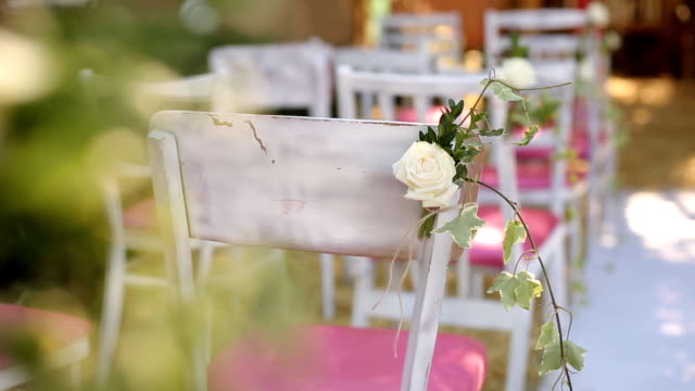 erstaunliche rustikale dekoration hochzeit zeremonie mit heu, stühle, floristische compoitions blume und hochzeitskleid hängt an einem baum im hintergrund. sommer land hochzeitskonzept - dekorative kunst stock-videos und b-roll-filmmaterial