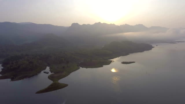 Amazing shot of beautiful sunrise on tranquil lake with fog on the mountain, Aerial video