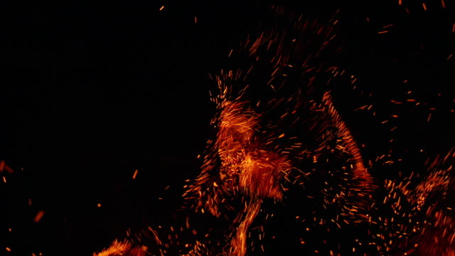 Amazing sparks and explosion clip to be used as a luma matte or track matte. Real embers flying around not a 3D particle render Real bonfire clip with flames and hot flying sparks and embers floating up into the night sky. Filmed in slow motion at 240fps bonfire stock videos & royalty-free footage